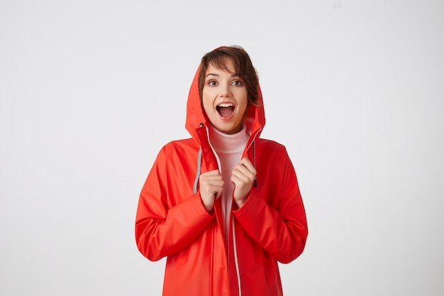 Portrait of young nice happy amazed short haired lady in red rain coat, looking with wide open mouth, hears cool news. standing.