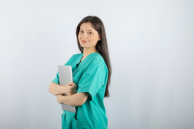Portrait of young nurse holding laptop on white.