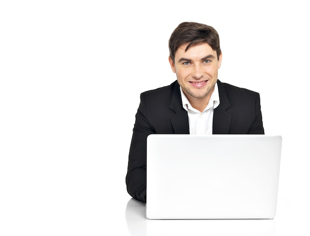Portrait of young office worker with laptop sitting on table isolated on white.