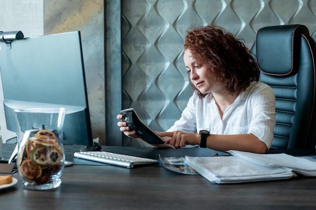 Ritratto di giovane donna di impiegato seduto alla scrivania in ufficio utilizzando la calcolatrice per calcolare qualcosa con seria espressione fiduciosa sul viso lavorando in ufficio