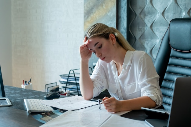 Portrait of young office worker woman sitting at office desk with documents looking tired and bored working in office