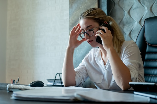 Portrait of young office worker woman sitting at office desk with documents talking on mobile phone nervous and stressed working in office