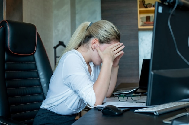 Portrait of young office worker woman sitting at office desk with documents using computer looking tired and bored having headache working in office