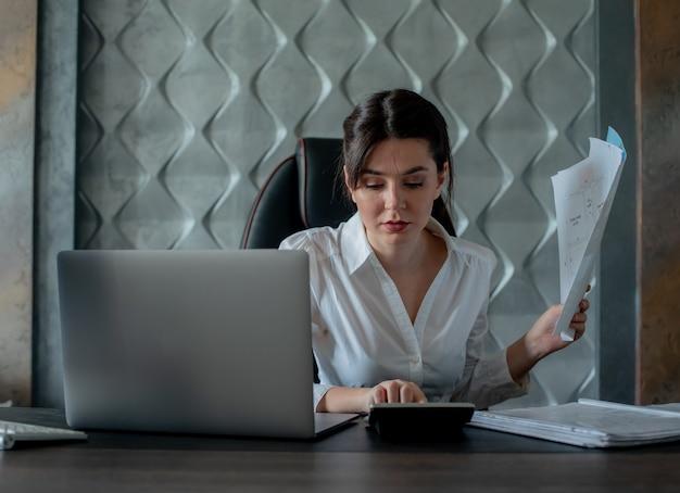 Ritratto di giovane donna di impiegato seduto alla scrivania in ufficio con computer portatile e documenti che calcolano con espressione seria concetto di ufficio processo di lavoro occupato e fiducioso