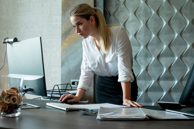 Portrait of young office worker woman standing at office desk with documents using computer with confident and serious expression on face working in office