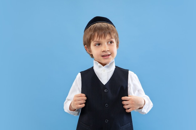 Portrait of a young orthodox jewish boy isolated on blue studio wall