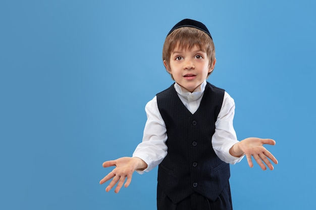 Portrait of a young orthodox jewish boy isolated on blue studio