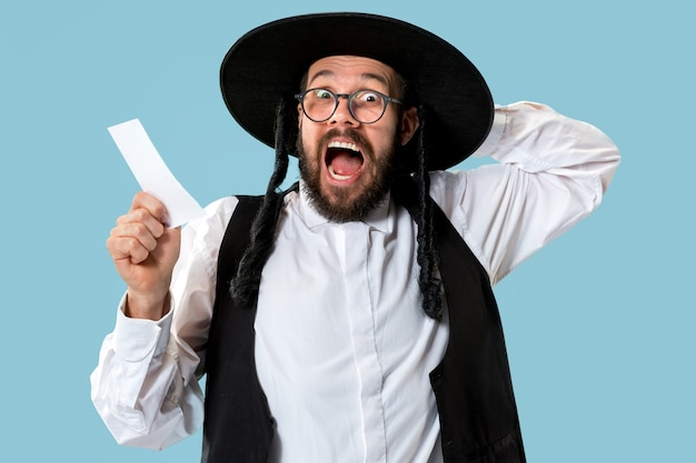 Portrait of a young orthodox jewish man with bet slip at studio
