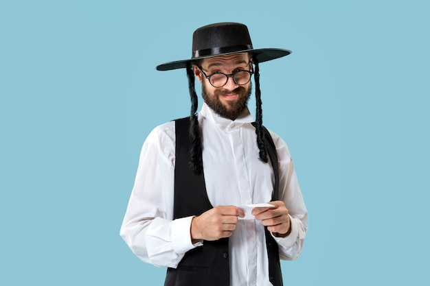 Portrait of a young orthodox jewish man with bet slip at