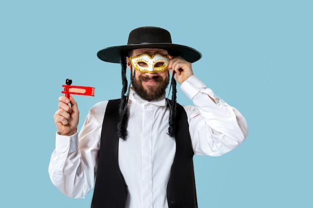 Ritratto di un giovane ebreo ortodosso con cricchetto grager in legno durante il festival purim. vacanza, celebrazione, ebraismo, concetto di religione.