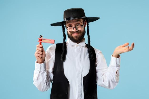 Ritratto di un giovane ebreo ortodosso con cricchetto grager in legno durante il festival purim. vacanza, celebrazione, ebraismo, tradizione, concetto di religione.