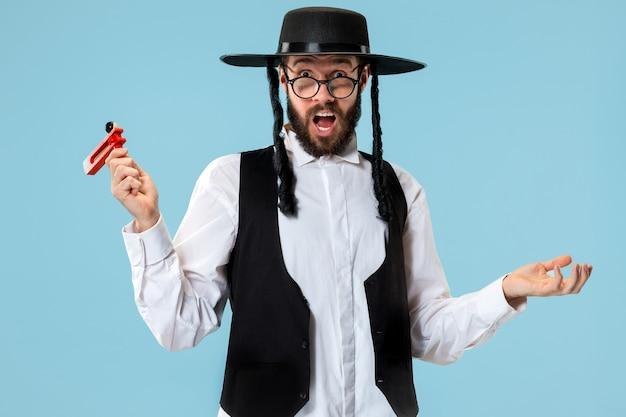 Ritratto di un giovane ebreo ortodosso con cricchetto grager in legno durante il festival purim.