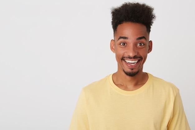 Ritratto di giovane ragazzo dalla pelle scura attraente felicissimo con la barba di essere in alto spirito
