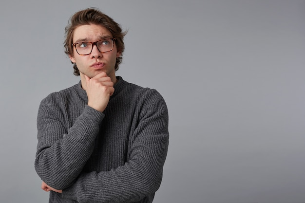 Portrait of young pensive man with glasses wears in gray sweater, stands over gray background with copy space on the right side, touches chin and looks up.