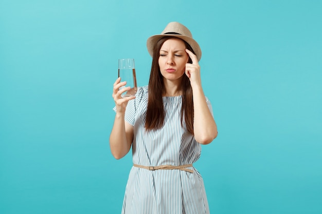 Portrait of young pensive woman in blue dress, hat holding and drinking clear fresh pure water from glass isolated on blue background. healthy lifestyle, people sincere emotions concept. copy space.