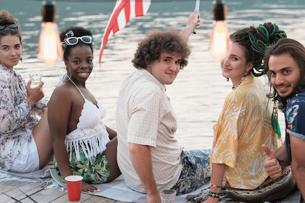 Portrait of young people sitting on a pier and smiling at camera they are at the party