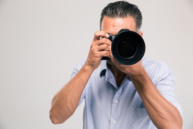 Portrait of a young photographer with camera isolated