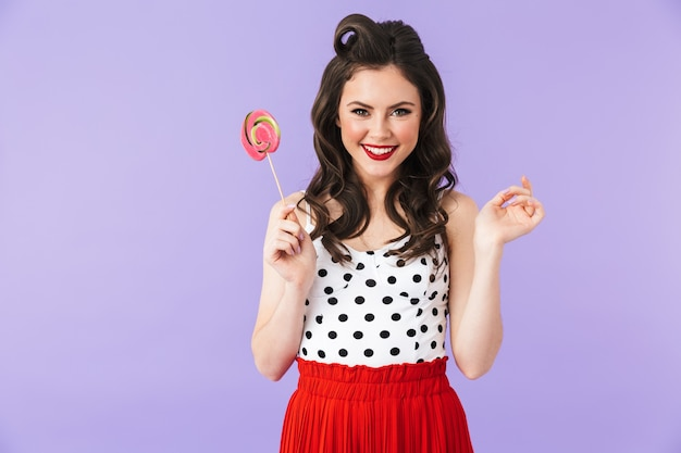 Portrait of young pin-up woman in vintage polka dot dress smiling while holding and eating colorful lollipop isolated over violet wall