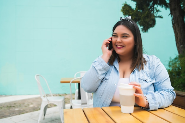 Portrait of young plus size woman talking on the phone while sitting outdoors at coffee shop.
