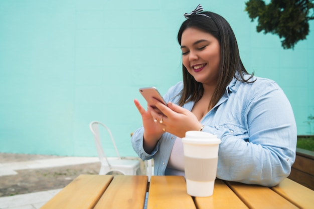 Portrait of young plus size woman using her mobile phone while sitting at coffee shop. communication and technology concept.