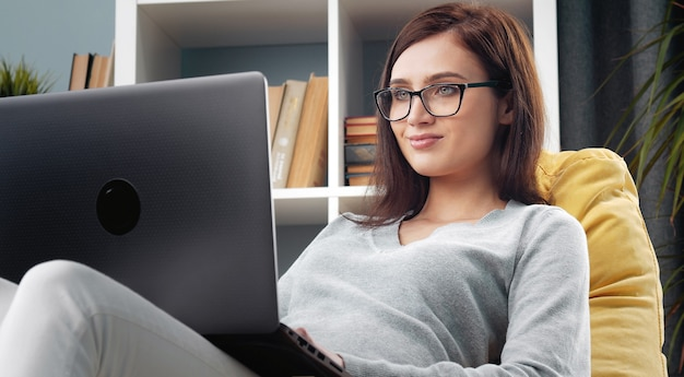 Portrait of young positive brunette sitting on beanbag chair with laptop on her knees at home