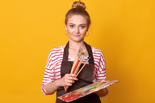 Portrait of young positive creative artist with many brushes and palette in both hands
