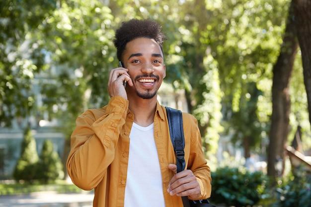 Ritratto di giovane ragazzo dalla pelle scura positivo in camicia gialla, passeggiate al parco, parlando sullo smartphone con il suo amico, distogliendo lo sguardo e ampiamente sorridente.