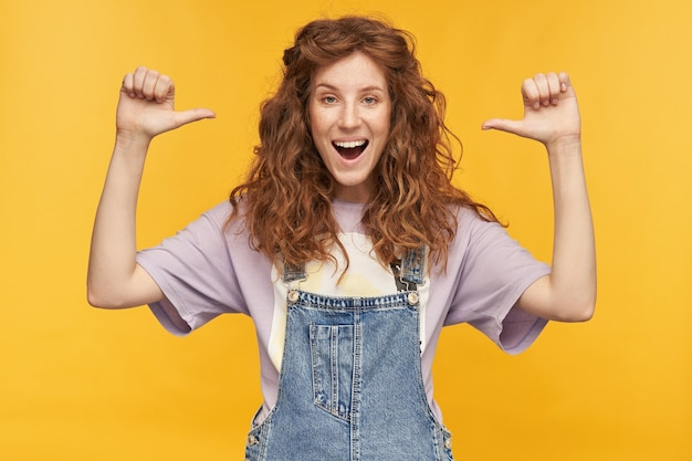 Portrait of young positive ginger woman, wears blue overalls and purple t-shirt, smiles broadly, enjoy herself, pointing with a finger at herself isolated over yellow wall