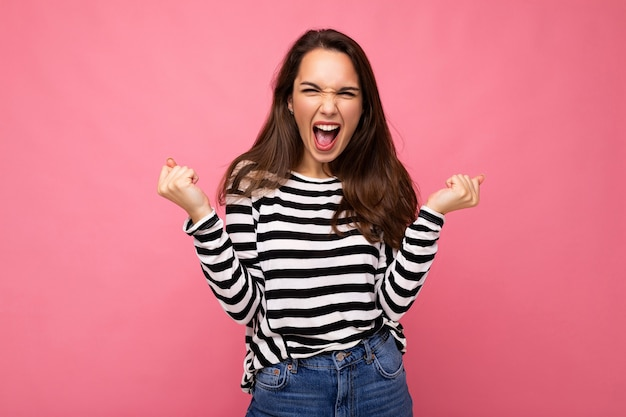 Portrait of young positive happy beautiful brunette woman with sincere emotions wearing casual striped pullover