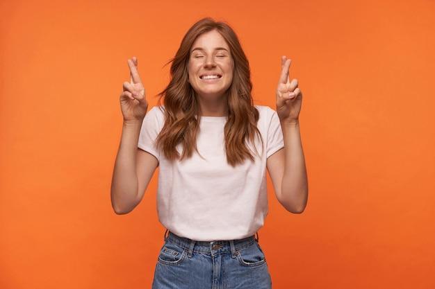 Ritratto di giovane donna dall'aspetto piacevole positivo che indossa maglietta casual e blue jeans, alzando le mani con le dita incrociate e esprimendo il desiderio con gli occhi chiusi