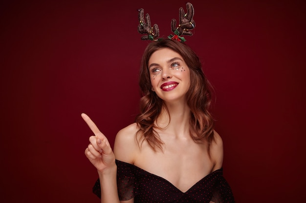 Portrait of young positive pretty brown haired female with wavy hairstyle looking happily aside and smiling sincerely, preparing for new year party and wearing holiday horns