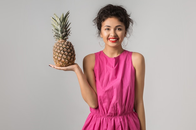 Portrait of young positive pretty woman in pink dress, holding pineapple, funny emotion, happy, smiling, summer style, fruit diet, looking in camera, thinking, asian, mixed race, isolated