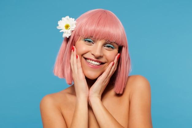 Ritratto di giovane donna graziosa positiva che indossa un fiore bianco nei suoi corti capelli rosa, tenendo i palmi sulle guance e sorridendo ampiamente