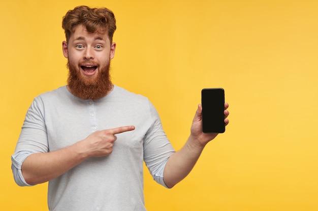 Ritratto di giovane uomo rosso positivo con una grande barba, che punta con un dito sul display del suo telefono con spazio vuoto nero per copia, sorride ampiamente. isolato su muro giallo