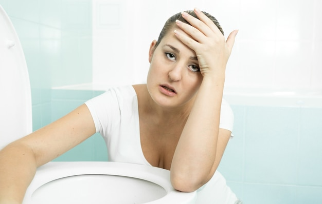 Portrait of young pregnant woman feeling sick and leaning on toilet