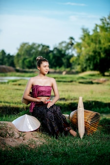 Portrait young pretty asian woman in beautiful thai traditional clothes at rice field, she sitting near fishing equipment