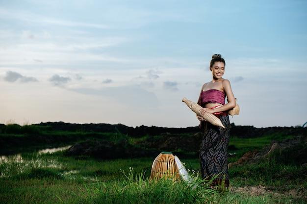 논에서 아름다운 태국 전통 옷을 입은 아름다운 젊은 아시아 여성, 서서 낚시 장비를 들고 있는 초상화