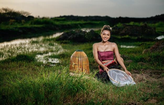 아름 다운 태국 전통 옷을 입고 논에서 낚시 장비 근처에 앉아 있는 초상화 젊고 예쁜 아시아 여성