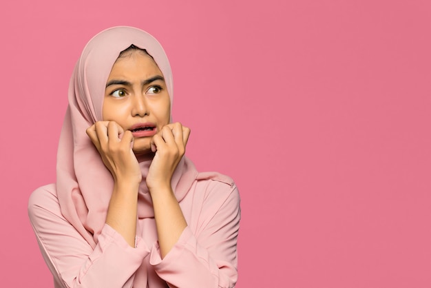 Portrait of young pretty asian woman panic and fear on pink background