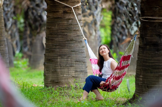 Portrait of  young pretty asian woman relaxing on hammock in the sugar palm forest.