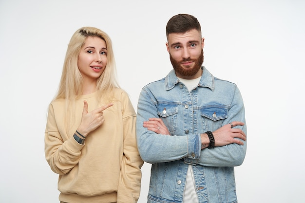 Portrait of young pretty blonde female in beige sweatshirt pointing positively on cute young brown haired bearded man with folded hands, posing on white