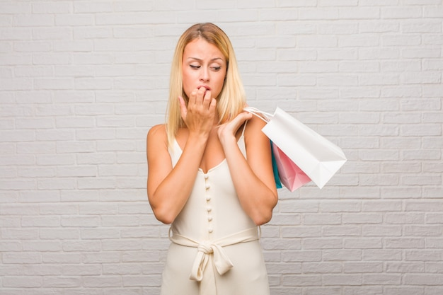 Portrait of young pretty blonde woman against a bricks wall biting nails, nervous and very anxious and scared for the future, feels panic and stress. holding shopping bags.