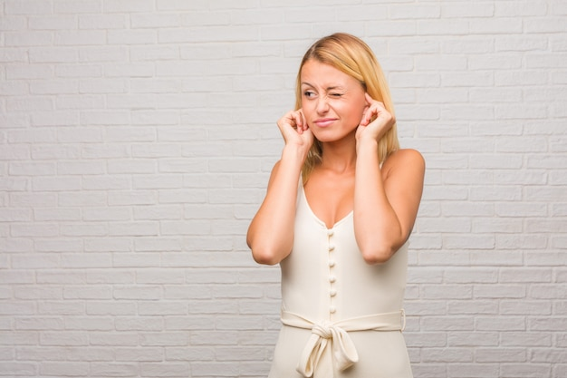 Portrait of young pretty blonde woman against a bricks wall covering ears with hands
