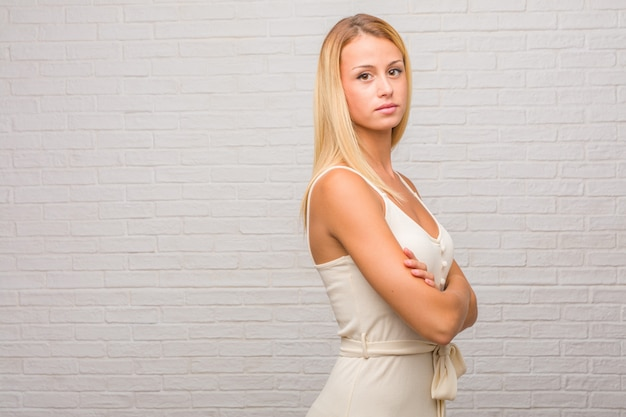 Portrait of young pretty blonde woman against a bricks wall crossing his arms, smiling and happy, being confident and friendly