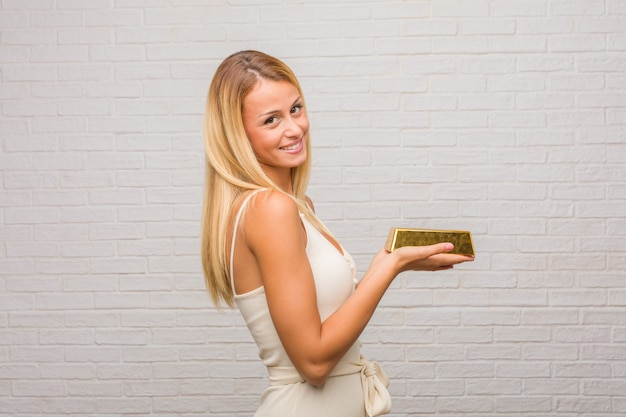 Portrait of young pretty blonde woman against a bricks wall holding something with hands, showing a product, smiling and cheerful, offering an imaginary object. holding a gold ingot.