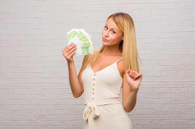 Portrait of young pretty blonde woman against a bricks wall listening to music, dancing and having fun, moving, shouting and expressing happiness, freedom concept. holding euro banknotes.
