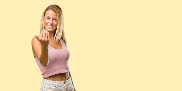 Portrait of young pretty blonde woman inviting to come, confident and smiling making a gesture with hand, being positive and friendly