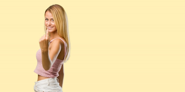 Portrait of young pretty blonde woman inviting to come