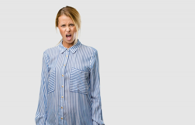 Portrait of a young pretty blonde woman very angry and upset, very tense, screaming furious, negative and crazy