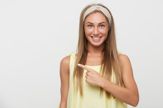 Ritratto di giovane bella donna bionda dagli occhi azzurri con trucco naturale guardando allegramente la fotocamera e mostrando da parte con l'indice, in piedi su sfondo bianco